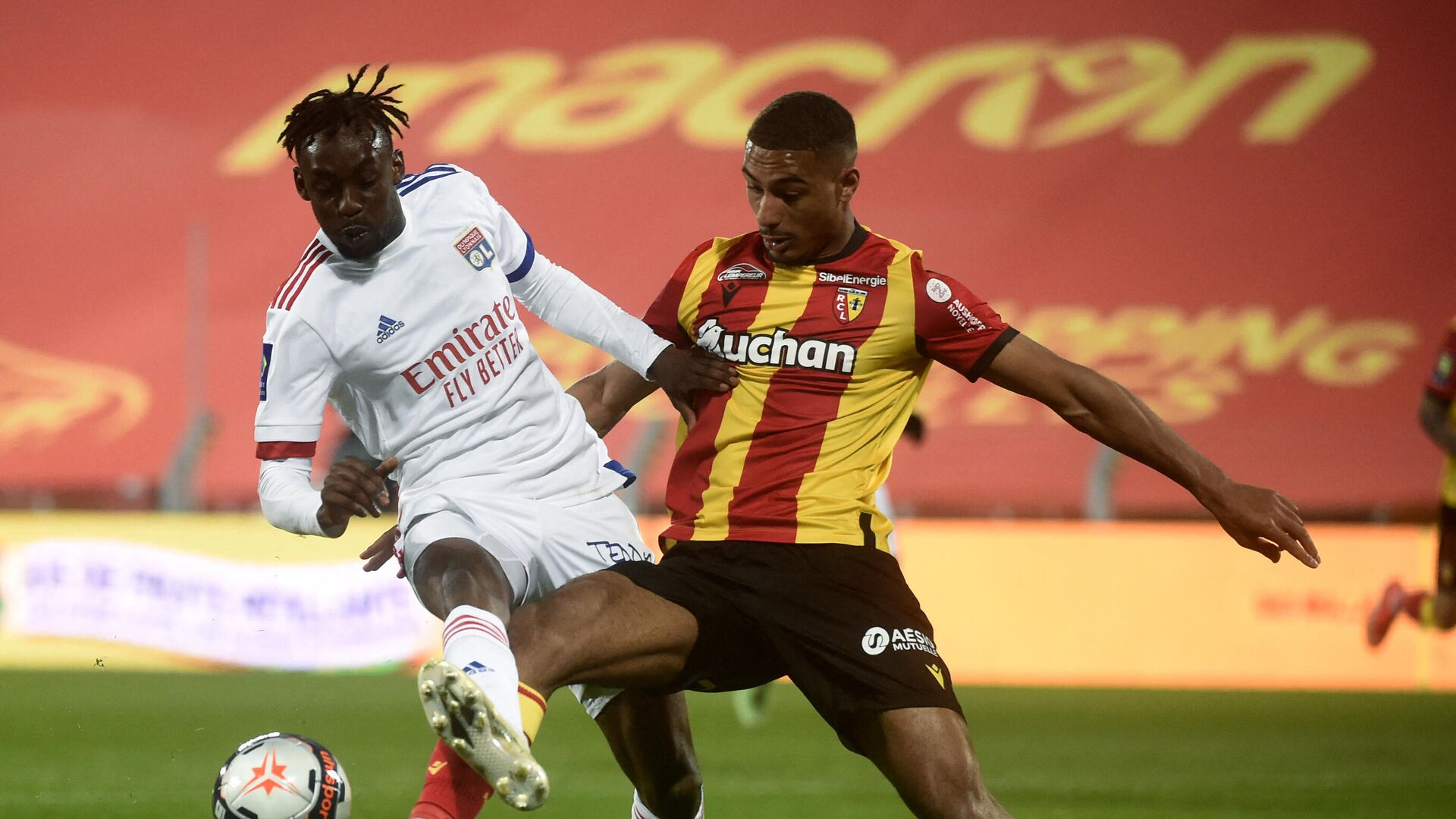Lens' French defender Loic Bade (R) and Lyon's Cameroonian forward Karl Toko Ekambi fight for the ball during the French L1 football match between Lens and Lyon at the Bollaert Stadium in Lens, on April 3, 2021. (Photo by FRANCOIS LO PRESTI / AFP) - РИА Новости, 1920, 04.04.2021