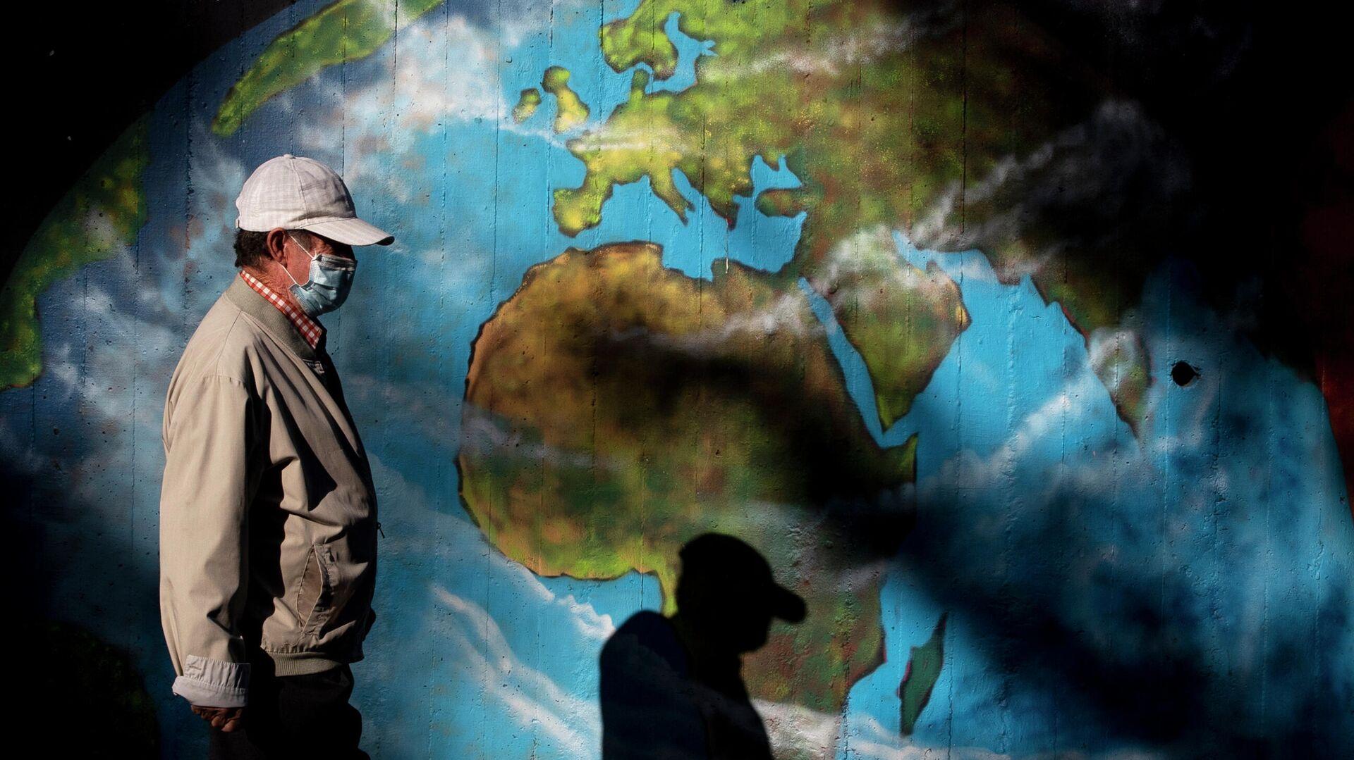 Мужчина в защитной маске проходит мимо граффити с изображением глобуса во время пандемии коронавируса в мире  - РИА Новости, 1920, 07.04.2021