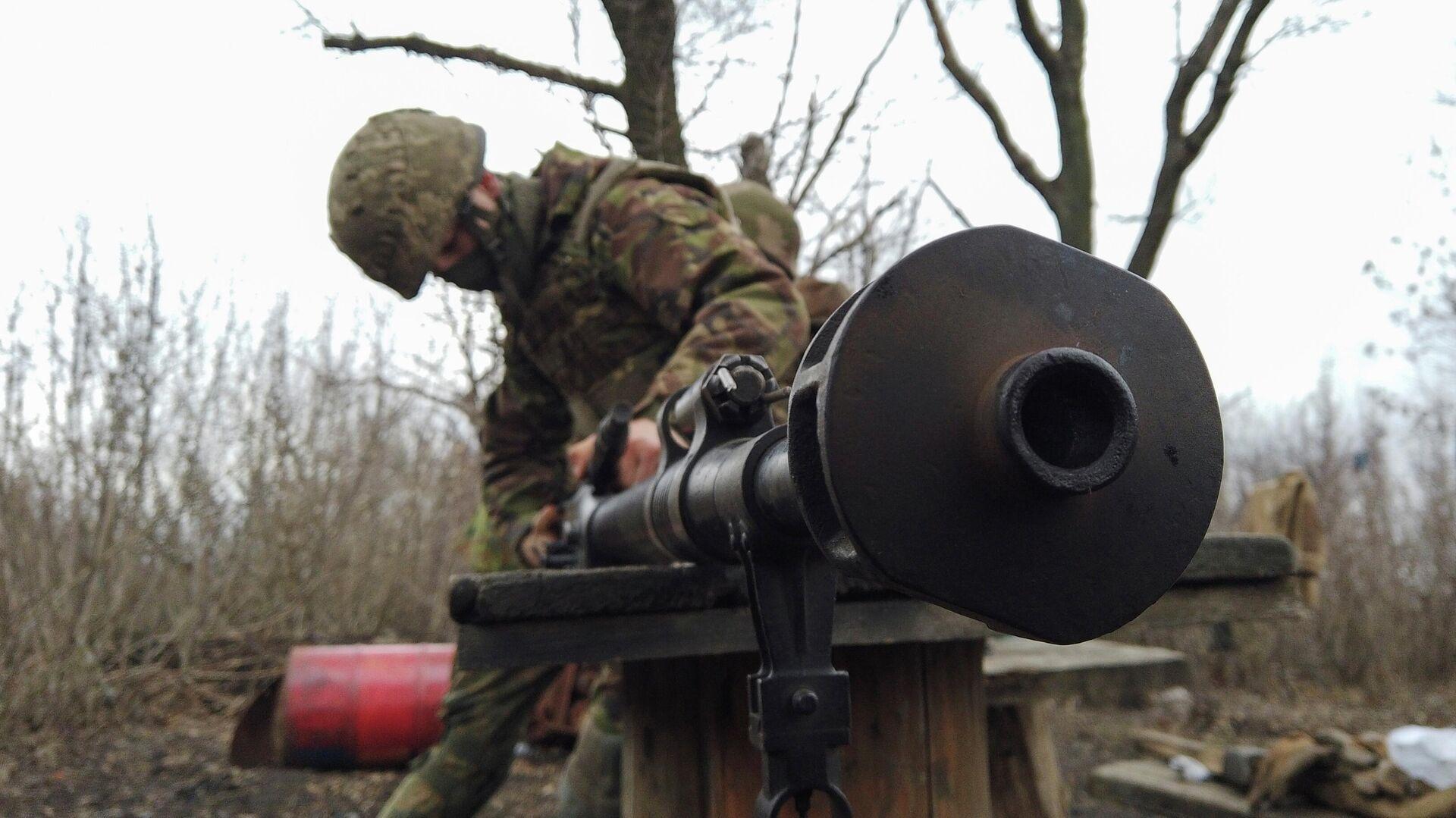 Военнослужащий украинских вооруженных сил чистит оружие на боевых позициях на линии разделения возле  города Донецк - РИА Новости, 1920, 08.04.2021
