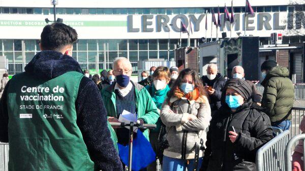 Местные жители стоят в очереди на вакцинацию от коронавируса в центре вакцинодром на стадионе Стад де Франс