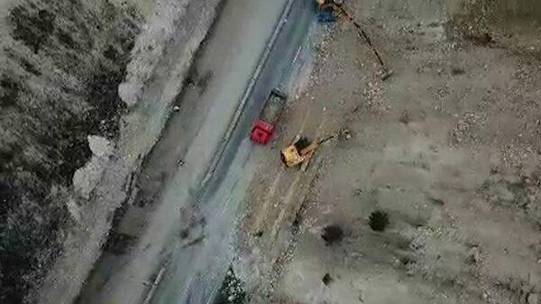 Техника разбирает завал грунта на трассе Таврида