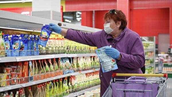 Женщина в защитной маске покупает майонез в супермаркете