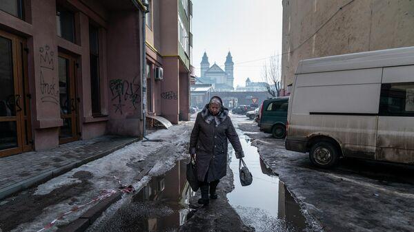 Женщина идет по улице в Ивано-Франковске, Украина