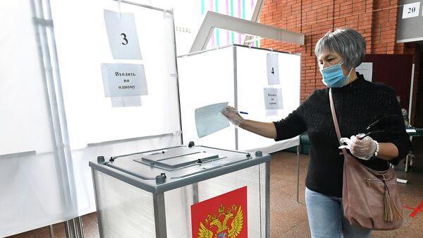 Женщина опускает бюллетень в урну для голосования