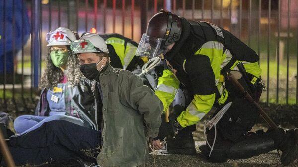 Полицейский штата Миннесота надевает наручники на медика, который был на акции протеста у полицейского участка в городе Бруклин-сентер