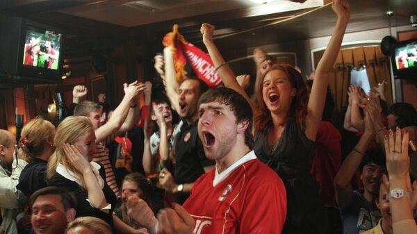 Фанаты Манчестер Юнайтед отмечают титул в московском баре.