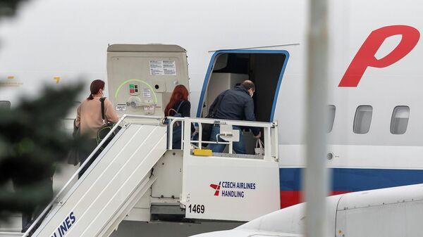 Российские дипломаты заходят в самолет авиакомпании Россия в аэропорту Праги