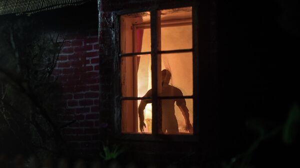 Мужчина в окне дома