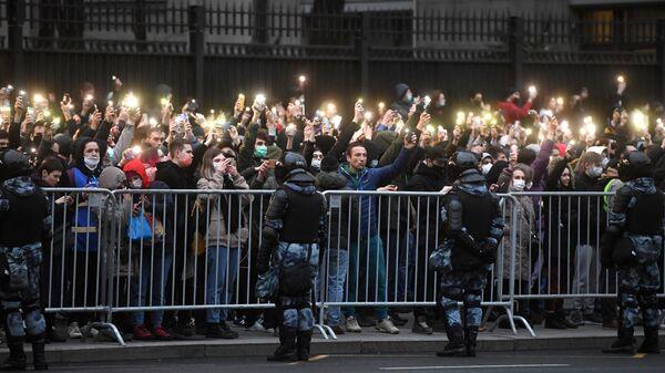 Участники несанкционированной акции в поддержку Алексея Навального держат смартфоны с включенными фонариками в Москве.