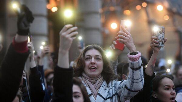 Участники несанкционированной акции в поддержку Алексея Навального держат смартфоны с включенными фонариками в Москве