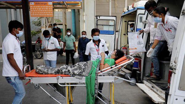 Пациента в кислородной маске везут в больницу для лечения COVID-19 в Ахмедабаде, Индия