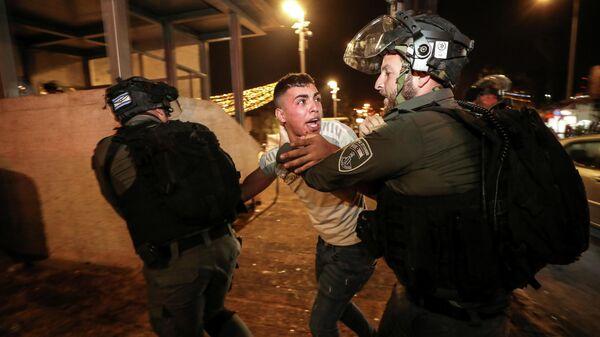 Сотрудники полиции задерживают участника беспорядков в Иерусалиме, Израиль