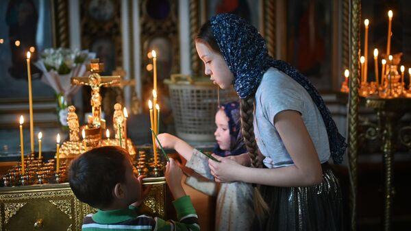Прихожане во время службы в преддверии праздника Входа Господня в Иерусалим в храме в честь Воздвижения Честного и Животворящего Креста Господня в Омске