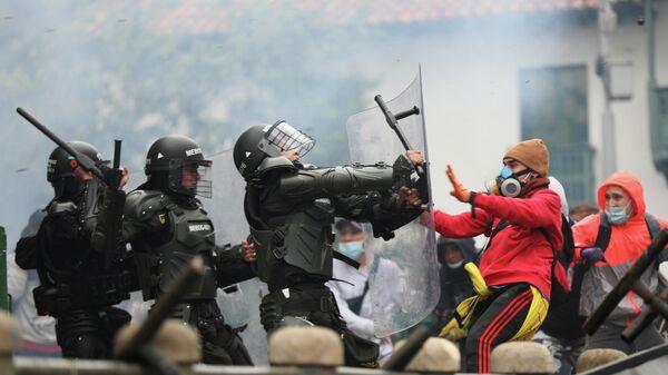 Столкновения демонстрантов с сотрудниками сил безопасности во время акции протеста против налоговой реформы правительства президента Ивана Дуке в Боготе, Колумбия. 28 апреля 2021 года