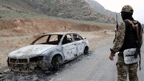 Военнослужащий Киргизии стоит у сгоревшей машины на границе Таджикистана и Киргизии в селе Кок-Таш