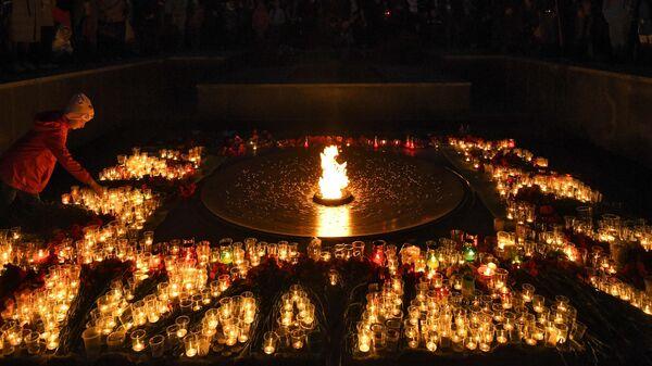 Люди зажигают свечи во время акции Свеча памяти на Монументе Славы в Новосибирске