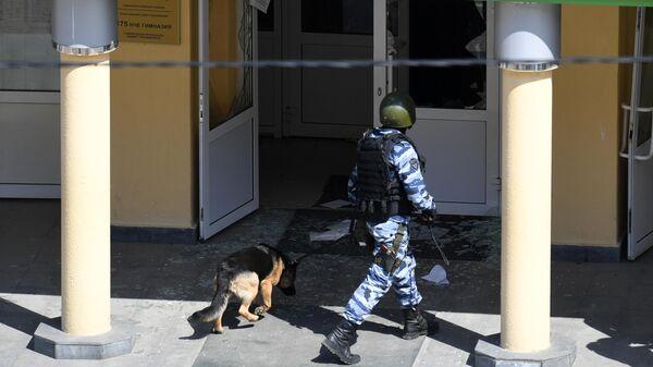 Сотрудник правоохранительных органов со служебной собакой у школы в Казани, где произошла стрельба