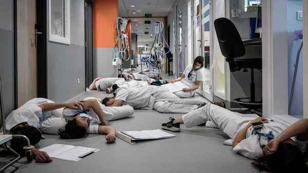Медперсонал лежат на полу в отделении интенсивной терапии во время демонстрации в Международный день медицинской сестры в больнице Mont Legia в Льеже, Бельгия