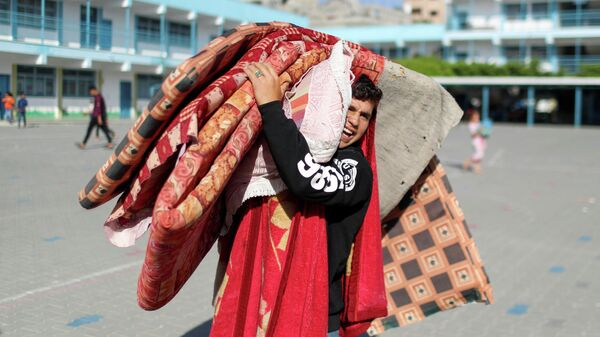 Палестинский юноша, бежавший из своего дома из-за израильских воздушных и артиллерийских ударов, несет вещи в убежище