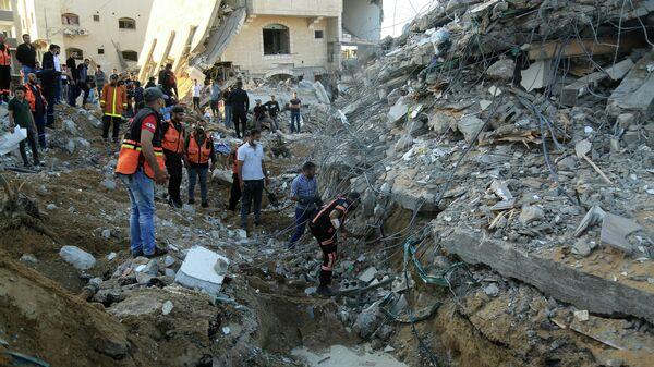 Палестинские медики на месте разрушенного дома в Газе