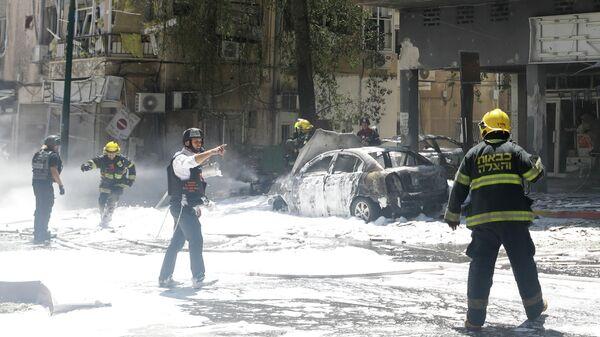 Пожарные ликвидируют последствия падения ракеты, выпущенной из Газы в пригороде Тель-Авива, Израиль