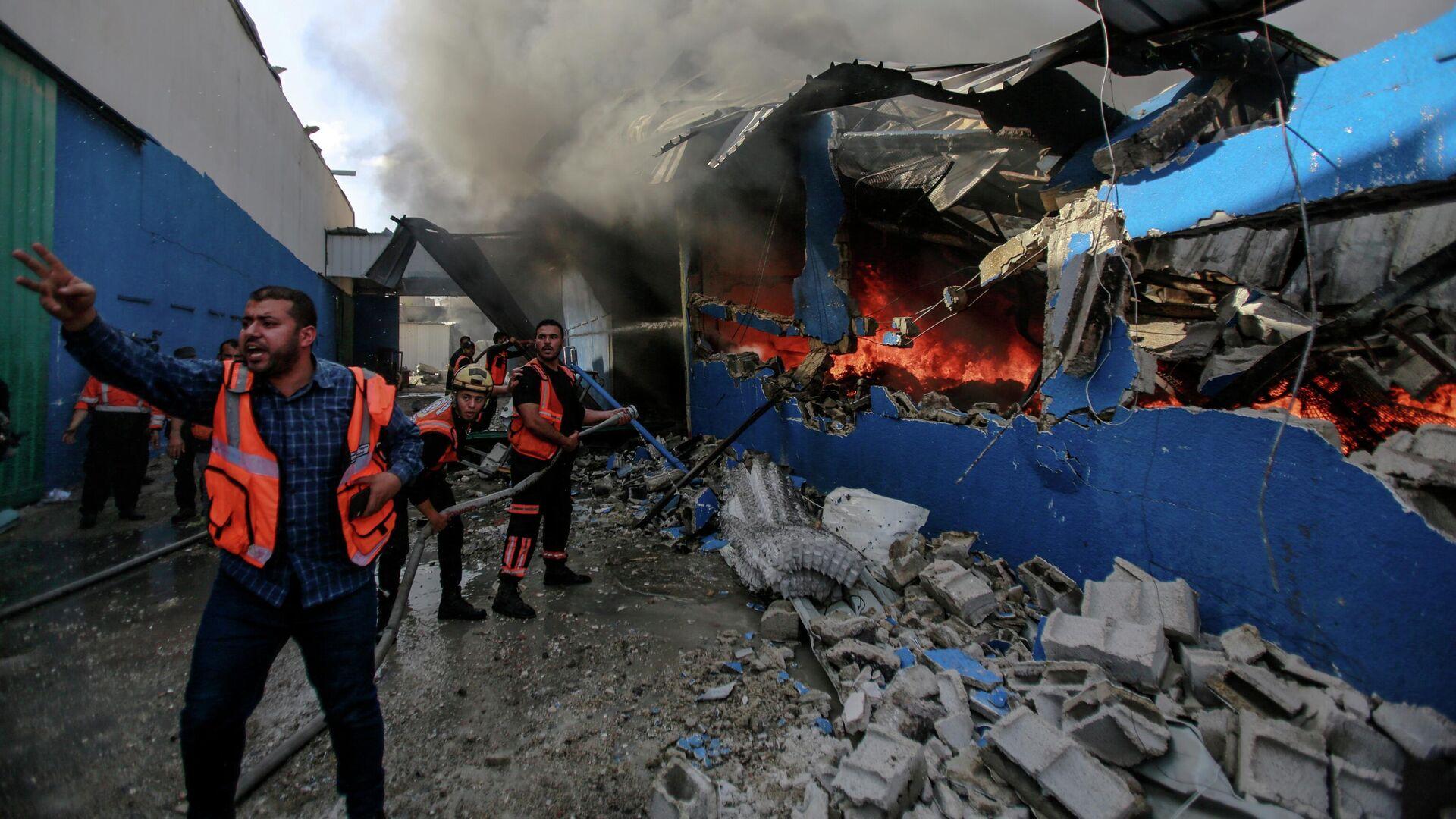 Члены Палестинской гражданской обороны тушат пожар на заводе по производству пенопласта в секторе Газа - РИА Новости, 1920, 17.05.2021