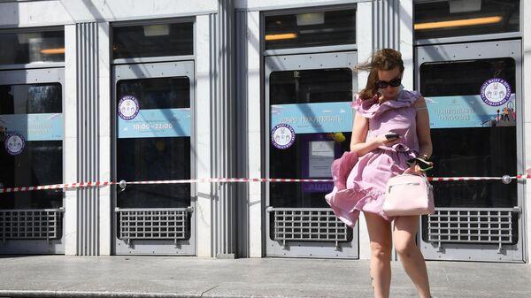 Девушка у здания Центрального детского магазина в Москве, опечатанного за нарушение профилактических мер