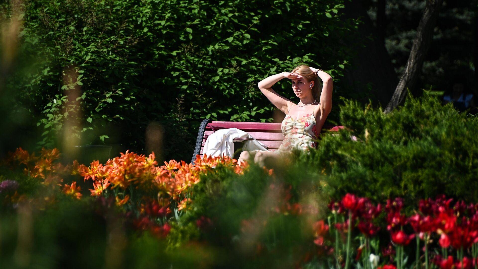 Девушка отдыхает под солнцем на скамейке в парке  - РИА Новости, 1920, 27.06.2021