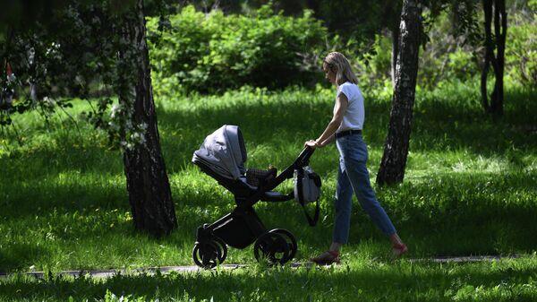 Женщина с ребенком на прогулке в сквере