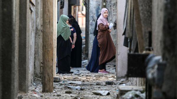 Жительницы Газы на улице, поврежденной в результате бомбардировки в секторе Газа