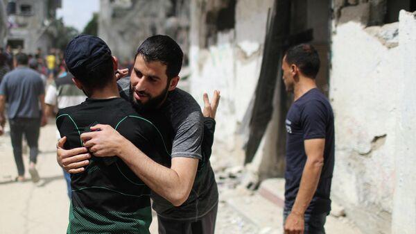 Палестинцы обнимаются после возвращения в свои разрушенные дома в Бейт-Хануне на севере сектора Газа
