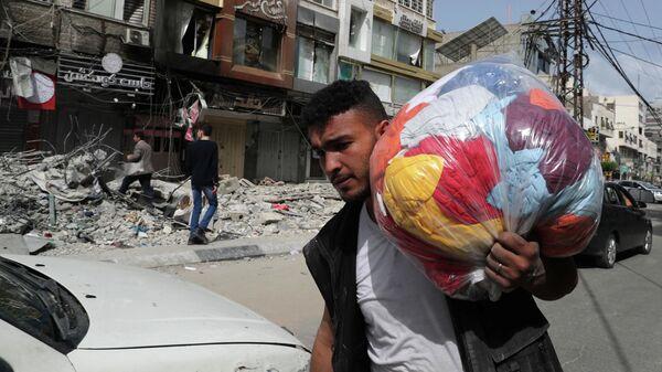 Палестинец проходит мимо разрушенных в результате бомбардировки зданий в секторе Газа, после объявления о прекращении огня между Израилем и ХАМАС