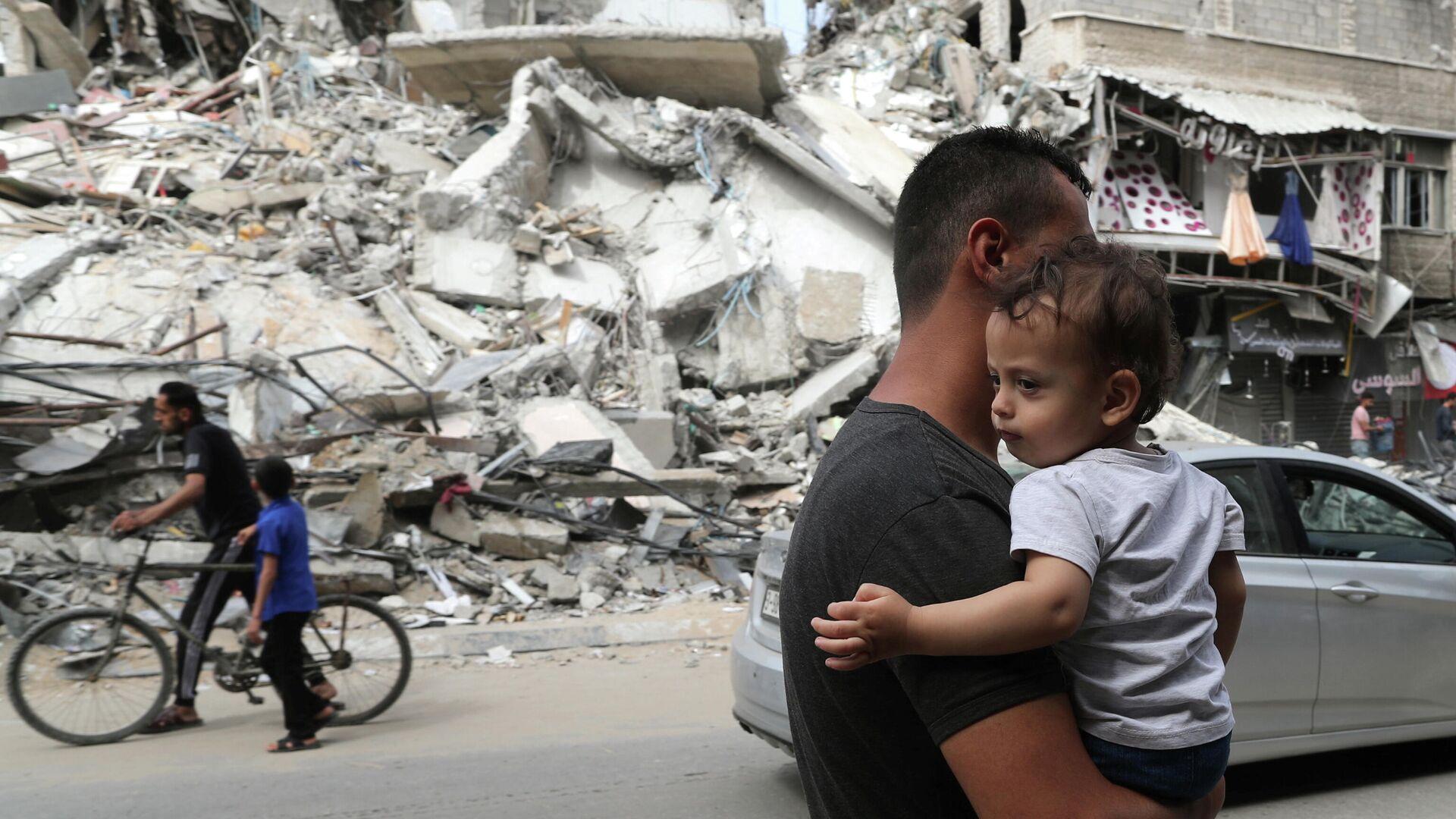 Палестинец с ребенком проходит мимо разрушенных в результате бомбардировки зданий в секторе Газа, после объявления о прекращении огня между Израилем и ХАМАС - РИА Новости, 1920, 01.06.2021