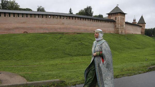 Экскурсовод в традиционной русской одежде на фоне Кремля в Великом Новгороде