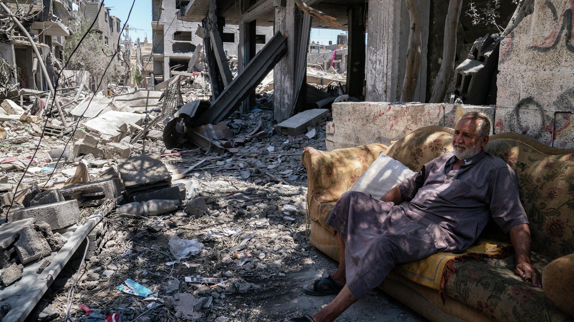 Житель Газы на улице, поврежденной в результате бомбардировки в секторе Газа - РИА Новости, 1920, 31.05.2021