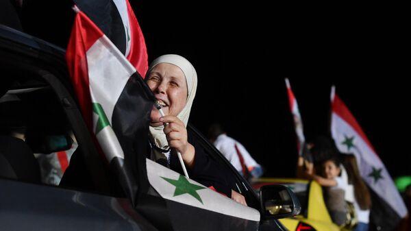 Женщина радуется победе на президентских выборах Башара Асада в Дамаске