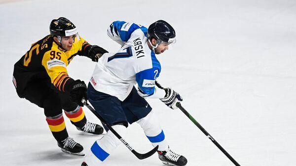 Слева направо: Фредерик Тиффельс (Германия) и Оливер Каски (Финляндия) в матче группового этапа чемпионата мира по хоккею 2021 между сборными командами Германии и Финляндии.