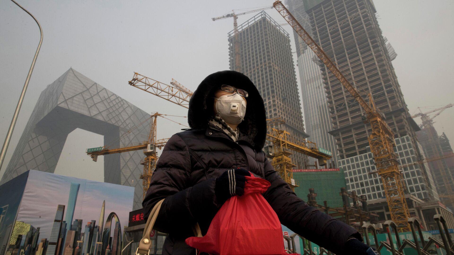 Девушка в защитной маске в Пекине на фоне строящихся зданий - РИА Новости, 1920, 31.05.2021