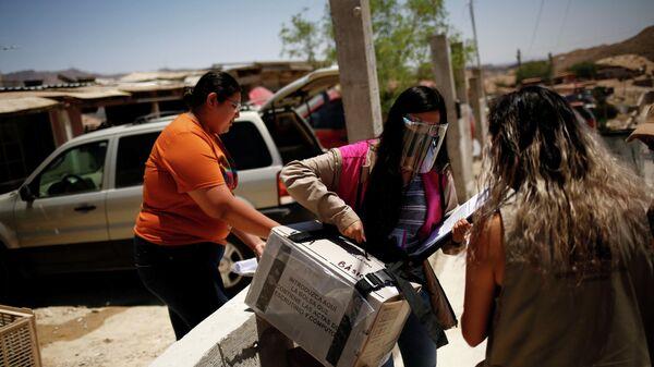 Сотрудник избирательного участка несет ящик с бланками для голосования, Мексика