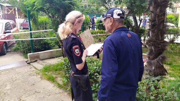 Сотрудник полиции опрашивает свидетелей на месте убийства судебных приставов в Адлере