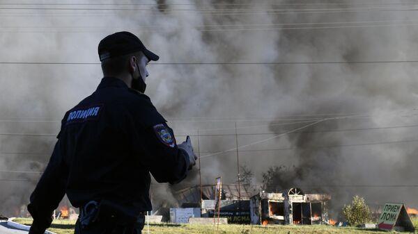 Сотрудник полиции у горящей автозаправки в Новосибирске