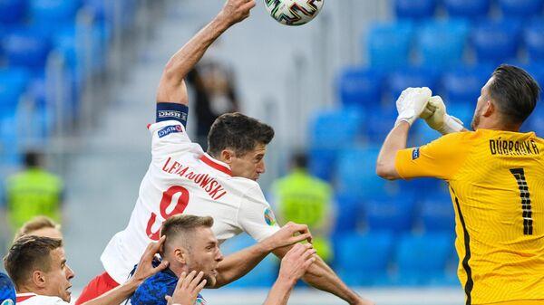Нападающий сборной Польши Роберт Левандовски (в центре) и вратарь сборной Словакии Мартин Дубравка (справа)
