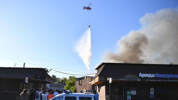 Пожарный вертолет тушит пожар над Лужнецкой набережной в Москве