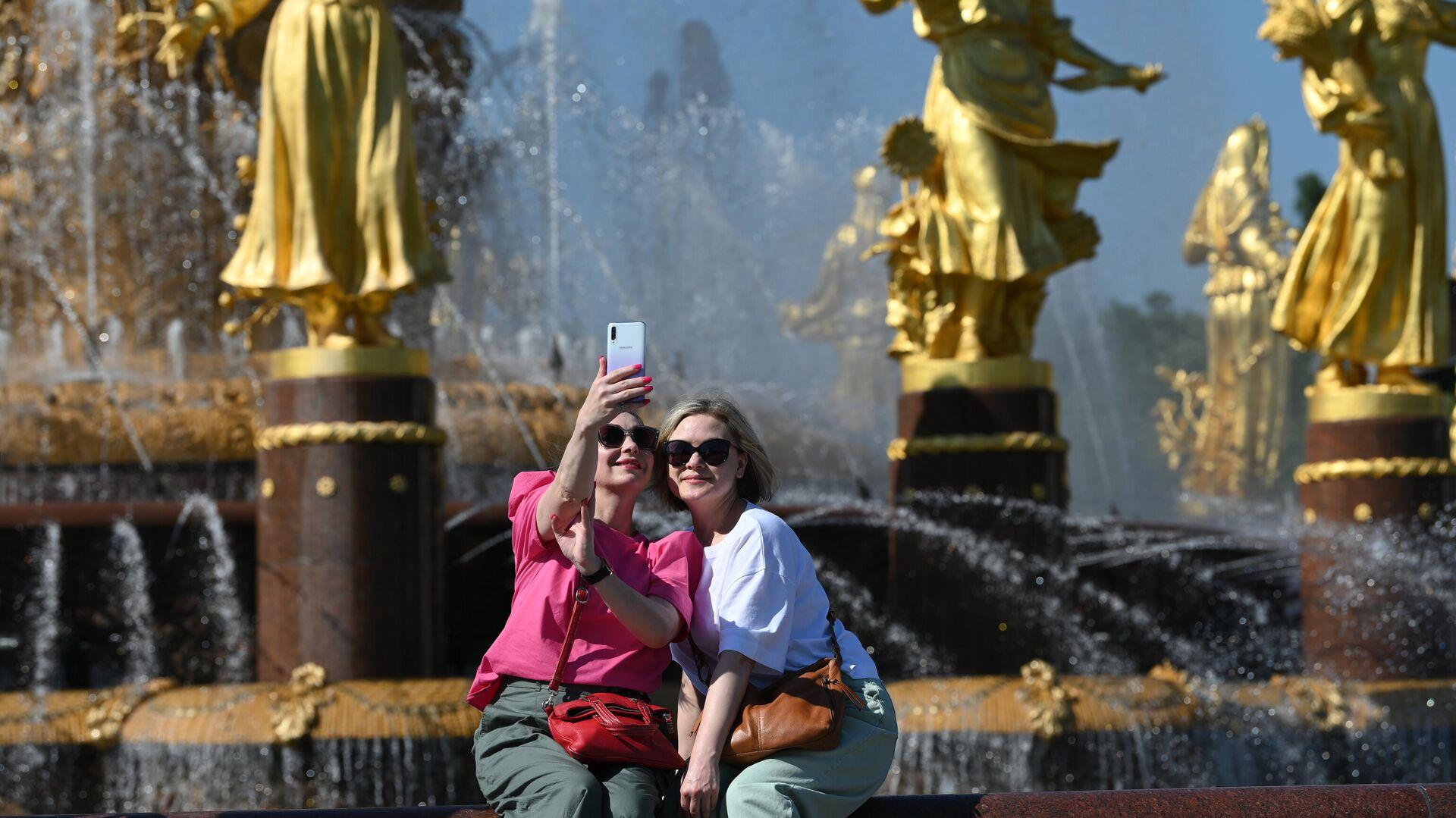 Девушки отдыхают в жаркую погоду у фонтана Дружба народов на ВДНХ - РИА Новости, 1920, 23.06.2021
