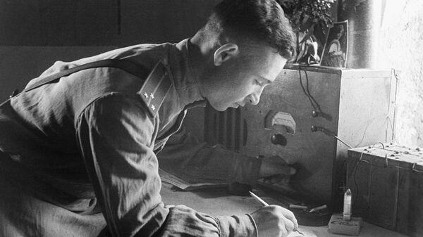 Корреспондент армейской газеты Слово бойца старший лейтенант Зиновий Шкапенюк за записью сводки Совинформбюро. 1944