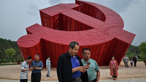 Люди рядом с памятником серпу и молоту в Нанниване, провинция Шэньси