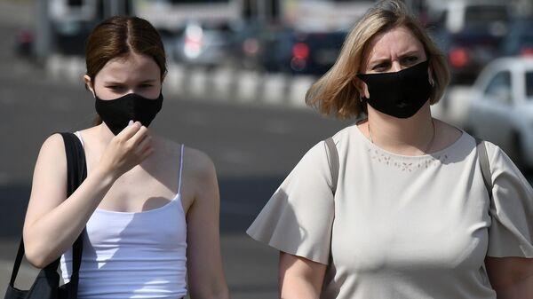 Прохожие в защитных масках на улице в центре Красноярска