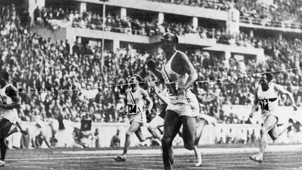 Американский атлет Джесси Оуэнс пересекает финишную черту в забеге на 100 метров на Олимпиаде 1936 года в Берлине