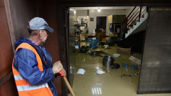 Сотрудник коммунальной службы устраняет последствия подтопления магазина в микрорайоне Кудепста Хостинского района Сочи