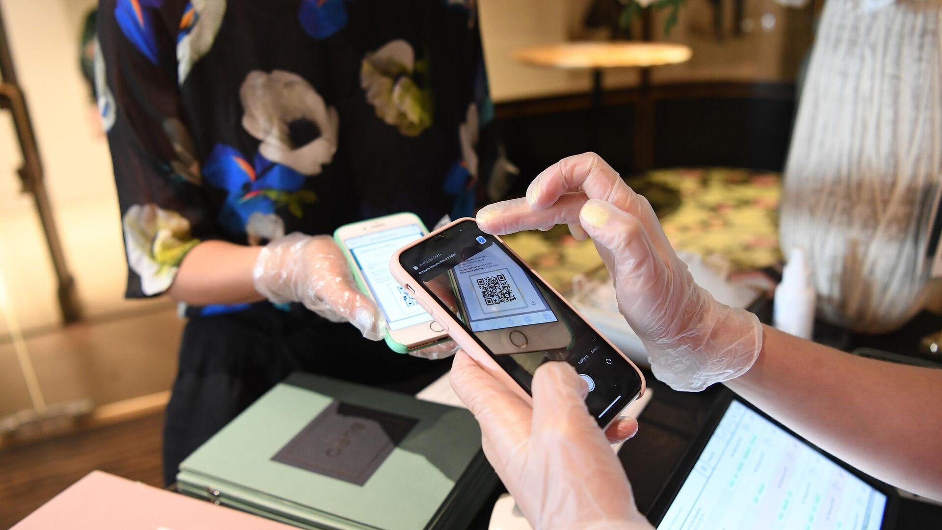 Хостес проверяет наличие и подлинность QR-кода у посетительницы перед посадкой за столик в ресторане BURO TSUM в Москве - РИА Новости, 1920, 06.07.2021